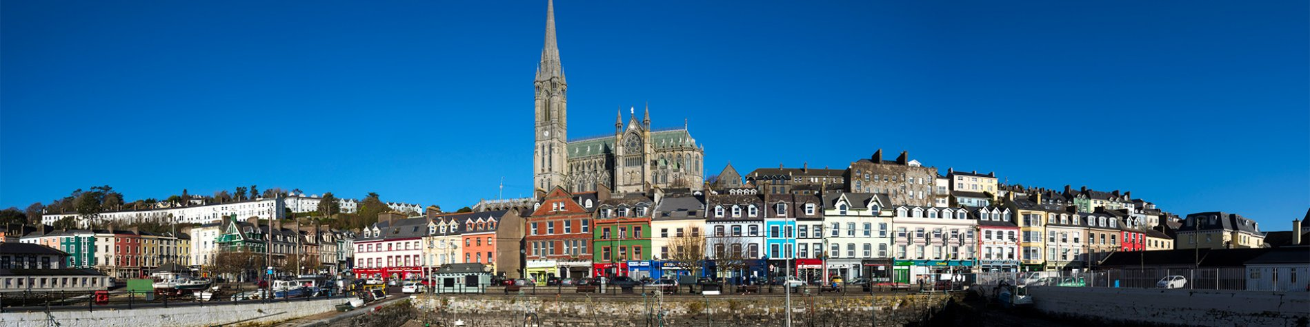 View of the Cathedral Church of St Colman and colourful houses from the sea - Cobh harbour