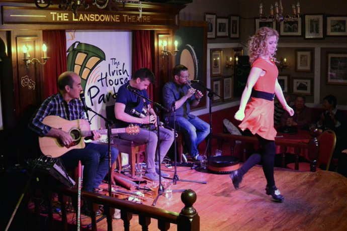 A group playing live music as a woman gets ready to dance at The Irish House Party
