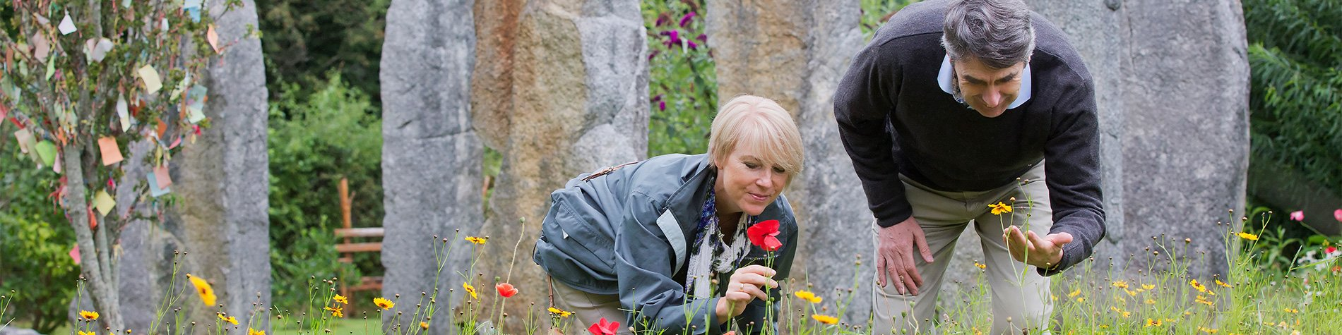 Man and woman smelling and observing flowers