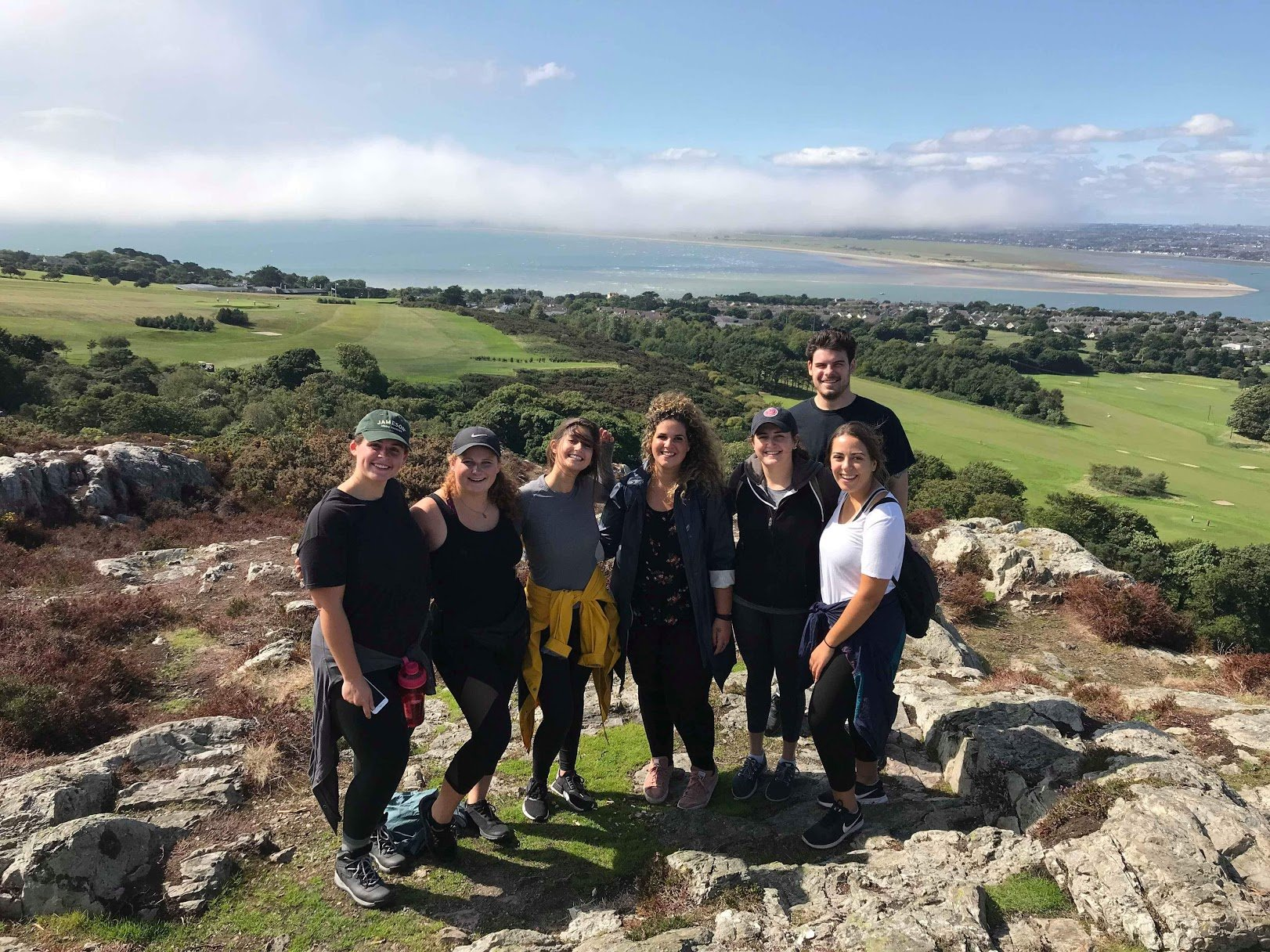 Group of Students posing for a photo on a hill in Howth on an adventure tour