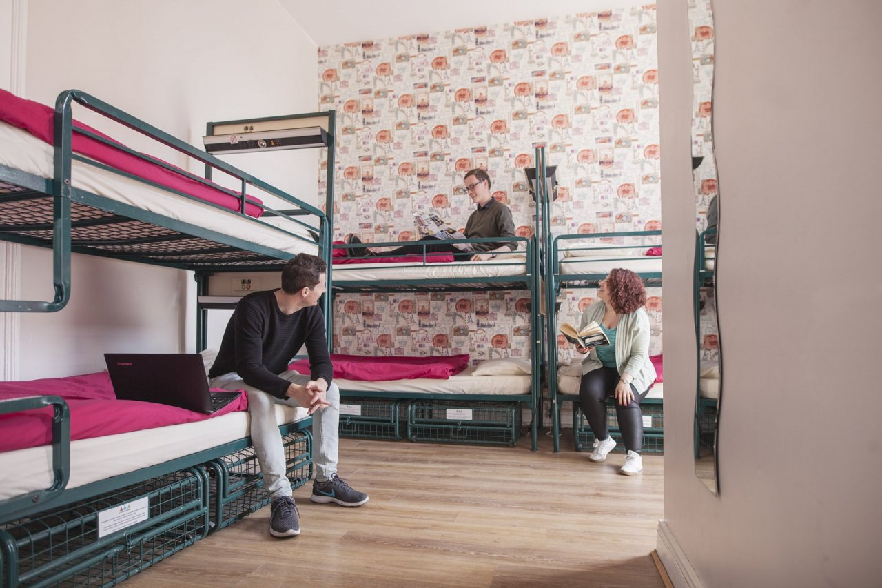 Group of Backpackers on Bunk Beds in the Multi-bed Room in Hostel