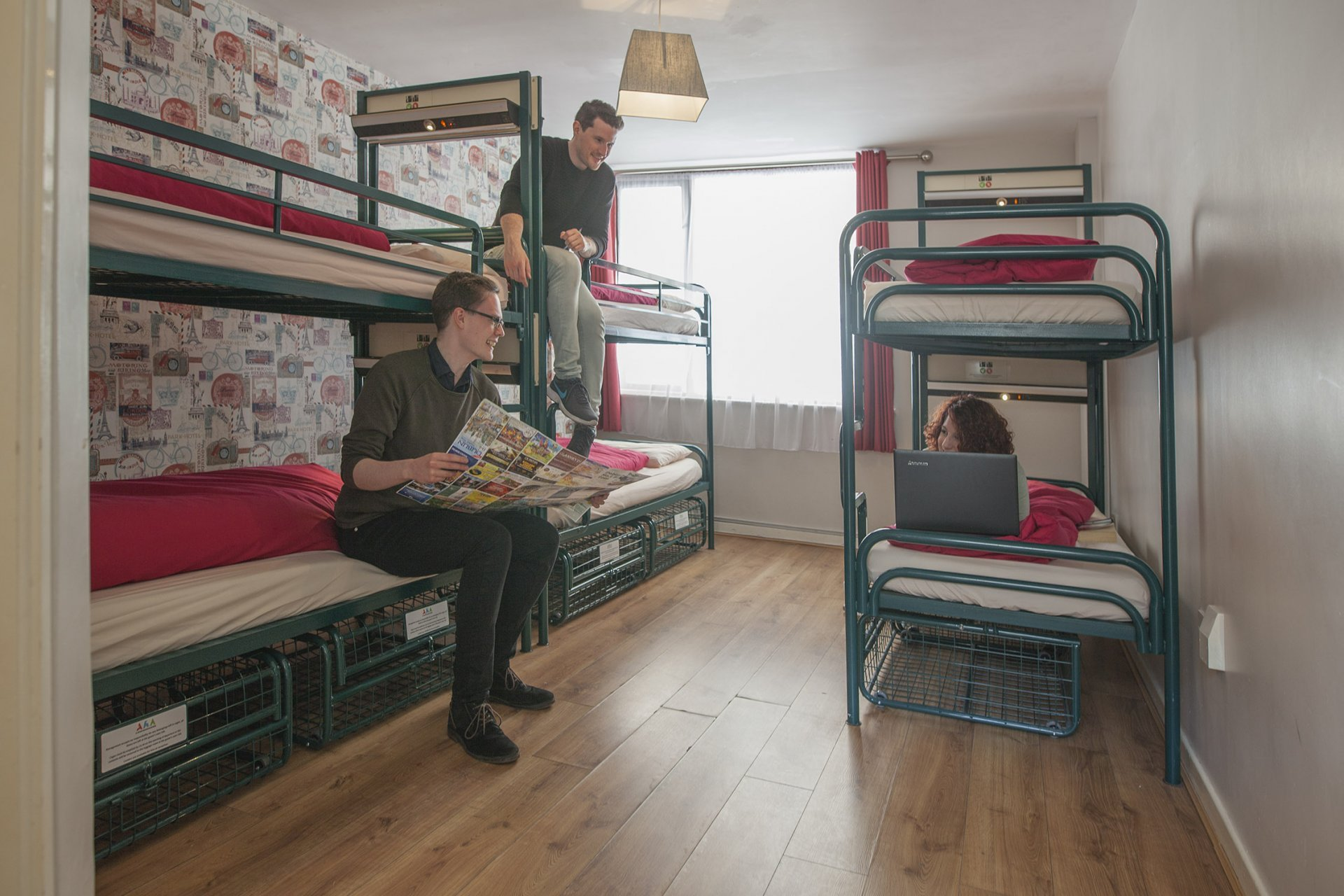 Three Backpackers Planning Day Trip on Bunk Beds in Hostel's Room