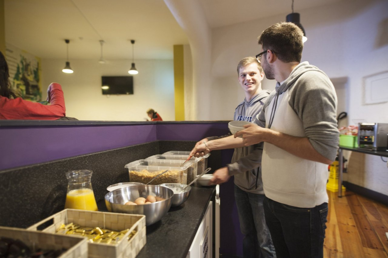 Tourist Residents Enjoying Continental Breakfast in Hostel