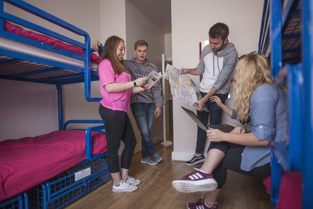Group of Students in Hostel Room Planning Day in Dublin Visible Bunk Beds with Secure Storage for Bags