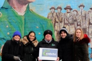 Group of People with Coiste Tour Guide at the back of them Mural with Irish Political Theme