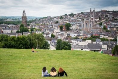 Students resting in a park watching the panoramic view of Cork city