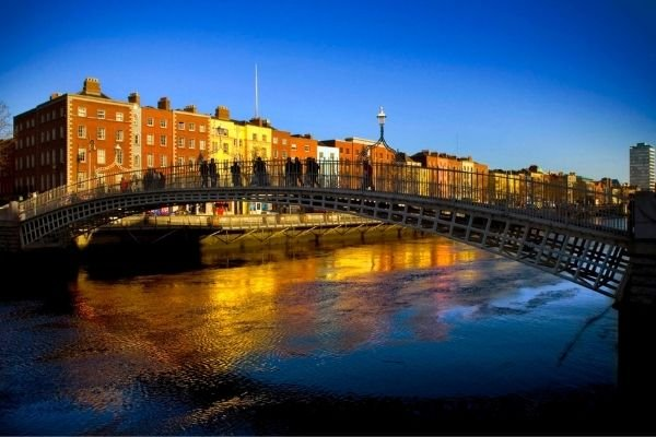 People crossing the Ha'Penny bridge in Dublin