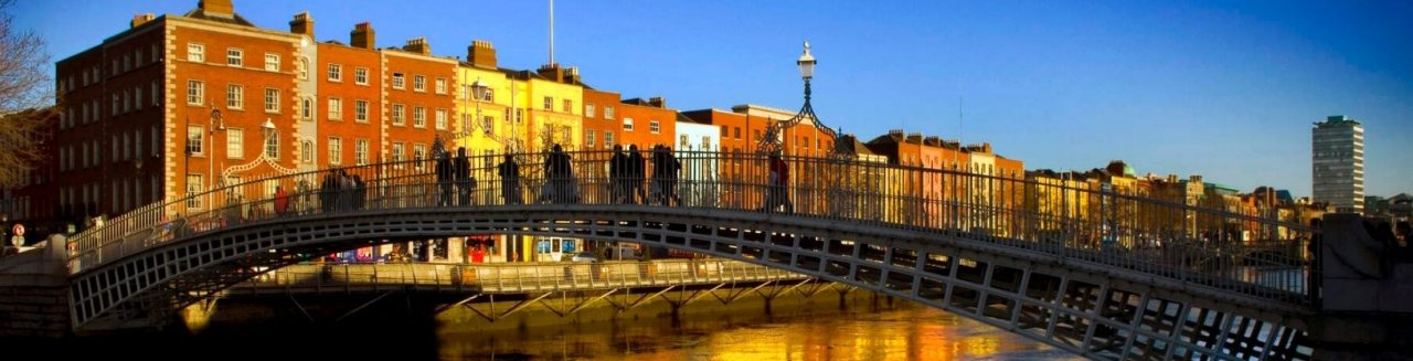 Group of people crossing the Ha'Penny Bridge on a sunny day in Dublin