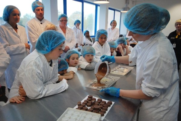 Group of visitors watching chocolate being made