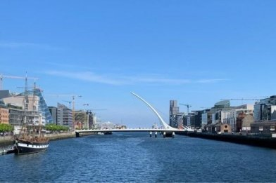 View of Dublin city from the river Liffey with the Jeanie Johnston and the Samuel Beckett bridge in the background