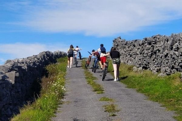 Students walking by their bikes up a hill on the Aran Islands
