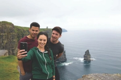 Students taking a picture in front of the Cliffs of Moher